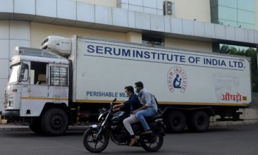 Coronavirus - FILE PHOTO: Men ride on a motorbike past a supply truck of India's Serum Institute, the world's largest maker of vaccines, which is working on a vaccine against the coronavirus disease (COVID-19) in Pune, India, May 18, 2020. Picture taken May 18, 2020. REUTERS/Euan Rocha/File Photo