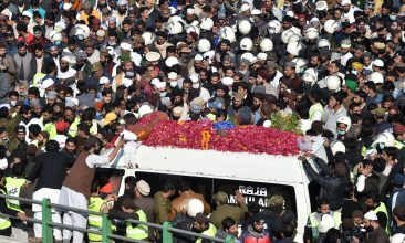 News - Activists and supporters of Tehreek-e-Labbaik Pakistan (TLP) gather around an ambulance carrying the coffin of Khadim Hussain Rizvi, founder of TLP, during his funeral procession in Lahore on November 21, 2020. - Massive crowds of maskless mourners gathered in Lahore on November 21 for the funeral of hardline Pakistani cleric Khadim Hussain Rizvi, who for years terrorised the country's religious minorities, incited riots and advocated the destruction of European nations in the name of fighting blasphemy. (Photo by Arif ALI / AFP) (Photo by ARIF ALI/AFP via Getty Images)