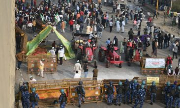 INDIA - Farmers gather next to their tractors as police stand guard at a road block to stop them from marching to New Delhi to protest against the central government's recent agricultural reforms at the Delhi-Uttar Pradesh state border in Ghazipur on December 1, 2020. (Photo by SAJJAD HUSSAIN/AFP via Getty Images)