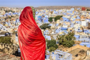 FEATURES - Young Indian woman looking at the view. The blue city of Jodhpur on the background. Jodhpur is known as the Blue City due to the vivid blue-painted houses around the Mehrangarh Fort.
