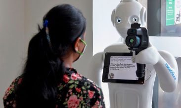 HEADLINE STORY - A patient gets her temperature checked by 'Mitra', a robot equipped with a thermal camera installed to register and conduct preliminary screening of patients before directing them to respective medical specialists to prevent the spread of COVID-19 coronavirus, at Fortis hospital in Bangalore on May 2, 2020. (Photo by MANJUNATH KIRAN/AFP via Getty Images)