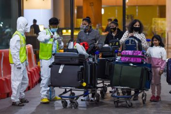 INDIA - Health workers keep vigil as passengers exit the Chhatrapati Shivaji International Airport in Mumbai. (Photo by PUNIT PARANJPE/AFP via Getty Images)