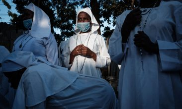 HEADLINE STORY - Worshippers of Legio Maria wearing face mask as a preventive measure against the spread of COVID-19 attend the Christmas prayer at their church in the Kibera slum of Nairobi, on December 25, 2020. (Photo by YASUYOSHI CHIBA / AFP) (Photo by YASUYOSHI CHIBA/AFP via Getty Images)