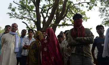 FEATURES - THE INSIDE STORY: Villagers, including the mothers of Padma and Lalli, stand in front of the tree where the two girls were found hanging in Katra Shahadatgunj, Uttar Pradesh, on May 31, 2014 (Photo credit: Chandan Khanna/AFP via Getty Images)