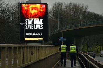 Coronavirus - Police officers walk past a Covid-19 information board alongside the  Clydeside Expressway in Glasgow on January 20, 2021. (Photo by ANDY BUCHANAN/AFP via Getty Images)