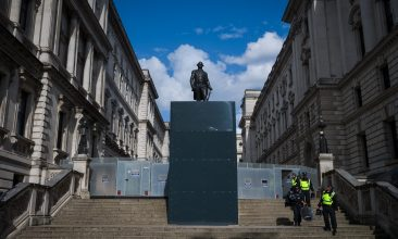 "FEATURES - LONDON, UNITED KINGDOM - JUNE 21: Police officers in riot clothing pass by a protected statue of Robert Clive, also known as ""Clive of India"", as they return to their vehicles after a Black Lives Matter rally in Parliament Square on June 21, 2020 in London, United Kingdom. Robert Clive is credited with establishing British rule in India for the East India Company through military campaigns against the French and Indian native rulers. Black Lives Matter protests are continuing across the UK following the death of African American George Floyd at the hands of police officers in Minneapolis on May 25, 2020. The movement has triggered the removal of statues with links to racism and the slave trade and has gained support from many high-profile celebrities and sports stars. (Photo by Leon Neal/Getty Images)"