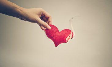 Column - Female hand giving a heart on fire / Dangerous love