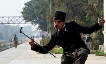 News - In this picture taken on February 9, 2021, street actor Usman Khan, dressed up as silent film star Charlie Chaplin, performs in the Pakistan's northwestern city of Peshawar. - Wearing a bowler hat and familiar toothbrush moustache, Pakistan's Usman Khan darts through traffic swinging a cane, teasing motorists and shopkeepers for laughs and a few rupees with a Charlie Chaplin impersonation that has become a viral sensation. (Photo by Abdul MAJEED / AFP) (Photo by ABDUL MAJEED/AFP via Getty Images)