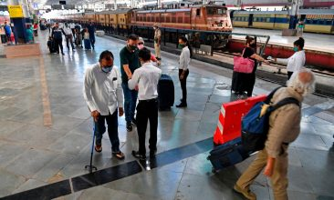 HEADLINE STORY - Health workers take body temperature readings of arriving passengers during the Covid-19 coronavirus screening at a railway terminus in Mumbai on February 22, 2021, as India's coronavirus cases passed 11 million. (Photo by INDRANIL MUKHERJEE/AFP via Getty Images)