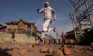 INDIA - FILE PHOTO: Kashmiris run for cover as Indian security forces (not pictured) fire teargas shells during clashes, after scrapping of the special constitutional status for Kashmir by the Indian government, in Srinagar, September 6, 2019. REUTERS/Danish Ismail/File Photo