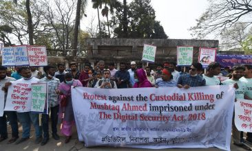BANGLADESH - Activists hold placards during a demonstration demanding the repeal of the Digital Security Act, in Dhaka on February 27, 2021 following the death of writer Mushtaq Ahmed in jail months after his arrest under internet laws which critics say are used to muzzle dissent. (Photo by Munir Uz zaman / AFP) (Photo by MUNIR UZ ZAMAN/AFP via Getty Images)