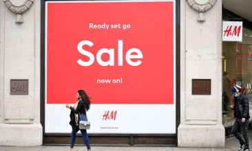 Business - Pedestrians wearing face coverings due to Covid-19, walk past a 'Sale' sign in the window of a closed H&M clothes store on a quiet Oxford Street in central London on March 24, 2021. (Photo by JUSTIN TALLIS/AFP via Getty Images)