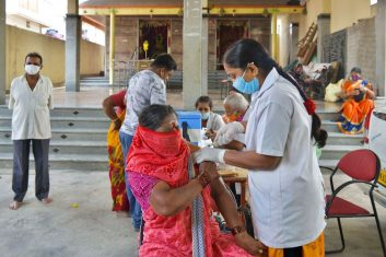 Coronavirus - A woman gets inoculated with a dose of the Covishield, AstraZeneca-Oxford's Covid-19 coronavirus vaccine, at a vaccination camp held inside a Hindu temple in Bangalore on April 9, 2021 as India surged past 13 million coronavirus cases. (Photo by MANJUNATH KIRAN/AFP via Getty Images)