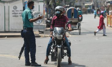 BANGLADESH - A policeman stops a motorist at a checkpoint as Bangladesh's authorities enforced a strict lockdown to combat the spread of the Covid-19 coronavirus, in Dhaka on April 14, 2021. (Photo by Munir uz zaman / AFP)