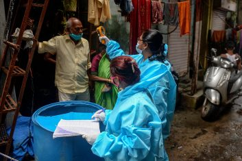 FEATURES - A health worker (R) wearing Personal Protective Equipments (PPE) checks the temperature of a resident inside a lane of the Dharavi slum during a door-to-door COVID-19 coronavirus screening in Mumbai on August 24, 2020. - India's confirmed coronavirus cases crossed the three million mark on August 23 with nearly 70,000 new infections, as the disease continues to surge in the world's second most-populous nation. (Photo by INDRANIL MUKHERJEE / AFP) (Photo by INDRANIL MUKHERJEE/AFP via Getty Images)