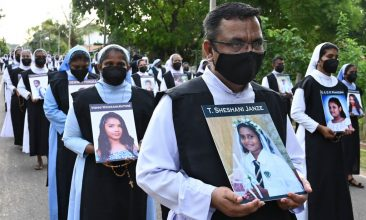 News - Catholic priests and nuns carry photos as they pay tribute of the victims killed in the 2019 Easter Sunday bombings, at St. Sebastian's Church in Negombo on April 21, 2021.  (Photo by LAKRUWAN WANNIARACHCHI/AFP via Getty Images)