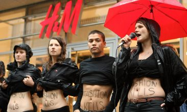 """BANGLADESH - Young activists from the labor rights group ver.di show their stomachs with the words """"Fashion Kills"""" written on them during a demonstration in the rain against working conditions at production sites used by the H&M clothing chain in Bangladesh on July 14, 2012 (Photo by Adam Berry/Getty Images)"""