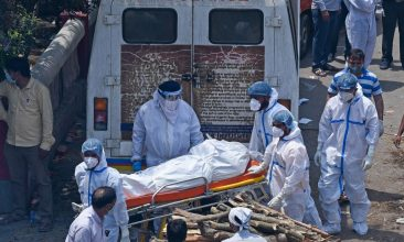 Comment - Family members and ambulance workers in PPE kits carry the bodies of victims who died of the Covid-19 coronavirus at a crematorium in New Delhi on April 27, 2021 (Photo: PRAKASH SINGH/AFP via Getty Images).
