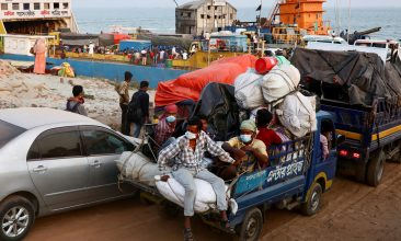 BANGLADESH - Migrant people and workers sit on a pickup van as they leave the city before the countrywide lockdown imposed as the coronavirus disease (COVID-19) cases increased, at Mawa ferry port in Munshiganj, Bangladesh, April 13, 2021. (REUTERS/Mohammad Ponir Hossain REFILE - CORRECTING TYPO IN COUNTRYWIDE)