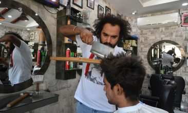 Arts and Culture - In this picture taken on April 8, 2021, Pakistani barber Ali Abbas uses a butcher knife to cut the hair of a customer at his shop in Lahore.  (Photo by Arif ALI / AFP) / TO GO WITH Pakistan-offbeat-barber (Photo by ARIF ALI/AFP via Getty Images)