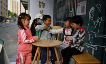 INTERNATIONAL - Children play outside a cafe in Beijing on May 11, 2021. (Photo by GREG BAKER/AFP via Getty Images)