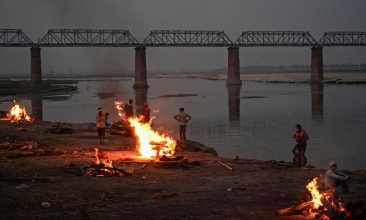 Covid in India - People watch unclaimed bodies burn on funeral pyres at a mass crematorium site on the banks of the Ganges river on May 05, 2021 in Allahabad, India.  (Photo by Ritesh Shukla/Getty Images)