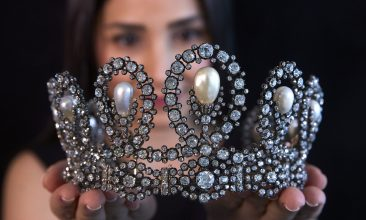 Business - A staff holds a diamond and pearl tiara passed down through generations of the Italian royal family during a preview at Sotheby's before their auction in Geneva, Switzerland, May 6, 2021.  REUTERS/Denis Balibouse