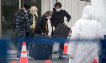 HEADLINE STORY - Passengers are assisted while loading bags into a taxi after disembarking from the quarantined Diamond Princess cruise ship, docked at the Daikoku Pier on February 20, 2020 in Yokohama, Japan. (Photo by Tomohiro Ohsumi/Getty Images)
