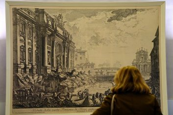 Arts and Culture - A visitor looks at a print of an engraving by Italian artist Piranesi showing the Trevi fountain (Photo: GABRIEL BOUYS/AFP via Getty Images).