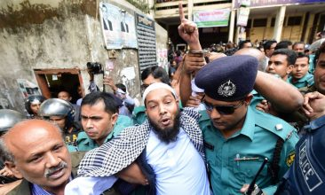 BANGLADESH - Police escort an Islamist extremist (C) to a prison van after his trial for allegedly plotting the Holey Artisan Bakery cafe attack, at a court in Dhaka on November 27, 2019. - Seven Islamist extremists have been sentenced to death by a Bangladesh court over a savage 2016 attack that killed 22 people including 18 foreigners at a Dhaka cafe popular with Westerners. (Photo by Munir UZ ZAMAN / AFP)