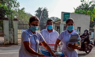 News - Nurses wearing facemasks cross a road as they push a trolley filled with leaflets outside the entrance of Sri Lanka's Infectious Diseases Hospital near Colombo on March 17, 2020. (Photo by LAKRUWAN WANNIARACHCHI/AFP via Getty Images)