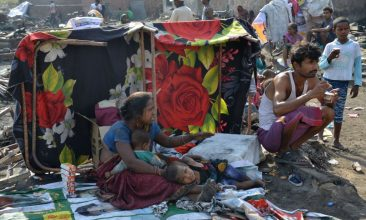 FEATURES - An Indian family sit together next to their surviving belongings a day after a fire that destroyed dwellings in a slum area in Amritsar on June 28, 2019. - No casualties were reported in the blaze that destroyed hundred of settlements in the slum area, the cause of which was still being investigated. (Photo by NARINDER NANU / AFP)        (Photo credit should read NARINDER NANU/AFP via Getty Images)