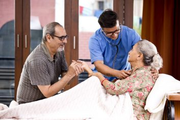 Comment - Home caregiver examining senior woman using stethoscope on bed