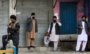 HEADLINE STORY - An Afghan security personnel (L) stands along with Sikhs near the site of an attack to a Sikh temple in Kabul on March 25, 2020. (Photo by STR/AFP via Getty Images)
