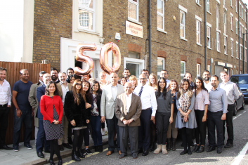 Remembering Ramniklal Solanki CBE - IMPARTING WISDOM: AMG staff with  Ramniklal Solanki (centre, in brown jacket)  and members of the Solanki family in front  of the company's London offices to mark  50 years since the launch of Garavi Gujarat