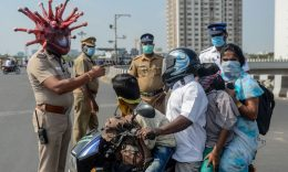 Coronavirus - Police inspector Rajesh Babu (C) wearing coronavirus-themed helmet speaks to a family on a motorbike at a checkpoint during a government-imposed nationwide lockdown as a preventive measure against the COVID-19 coronavirus in Chennai on March 28, 2020.  (Photo by ARUN SANKAR/AFP via Getty Images)