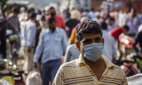 Coronavirus - NEW DELHI, INDIA - MARCH 26: An Indian man covering his face with a mask walks  in a crowded Mandi (market place), as nationwide lockdown continues over highly contagious novel coronavirus on March 26, 2020 in New Delhi, India. India is under a 21-day lockdown to fight the spread of Covid-19 infections and while the security personnel on the roads are enforcing the restrictions in many cases by using force, the workers of country's unorganized sector are bearing the brunt of the curfew-like situation. According to the international labour organisations India's  90% workforce is employed in the informal sector and  most do not have access to pensions, sick leave, paid leave or any kind of insurance. Reports on Thursday said that Prime Minister Narendra Modi's government is preparing a massive bailout to reach to the underprivileged sections of the country and will hand over the dole through direct cash transfers. (Photo by Yawar Nazir/Getty Images)